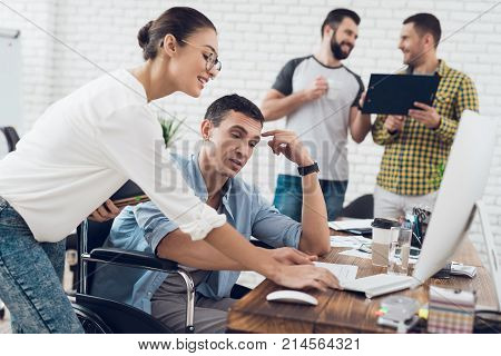 A man in a wheelchair is making a conversation with a girl. They are working in a bright office. They trying to solve a problem and smiling. Colleagues behind them is solving working issues.