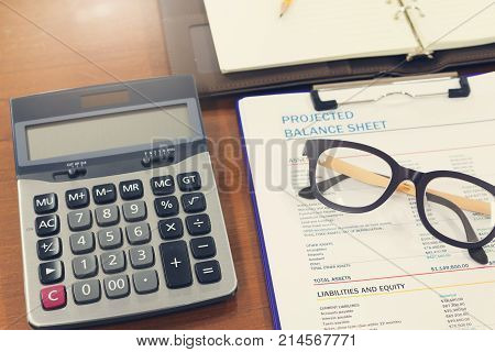 Business And Finance Concept Of Analysis Chart, Eyeglasses And Calculator On Office Desk