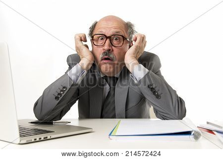 senior mature business man with bald head on his 60s working stressed and frustrated at office computer laptop desk looking desperate and overwhelmed in job mistake and problem concept