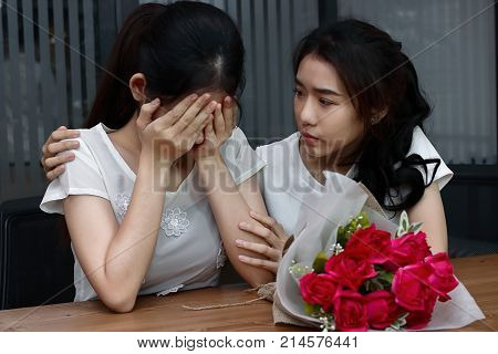 Stressed young Asian woman supporting depressed crying female friend in living room. Break up or best relationship concept.