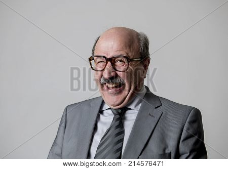 portrait of 60s bald senior happy business man gesturing funny and comic in laughter and fun face expression looking happy and cheerful isolated on grey background in satisfied worker or director concept