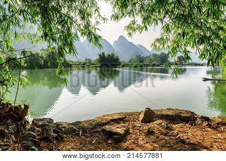 View Of The Yulong River And Karst Mountains Through Foliage