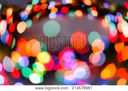 Color garland wreath background, unfocused. Christmas or other holiday decorations, garland illumination bokeh, copy space