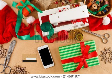Creative diy craft hobby. Wrapping christmas present boxes with satin ribbon. Christmas online shopping. Smartphone, credit card with copy space, preparing for winter holidays concept, top view