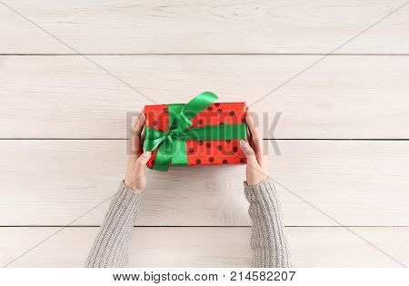 Gift wrapping background. Female hands holding handmade present box in red dotted paper against white wooden table background. Bithday or christmas preparation concept, top view, copy space