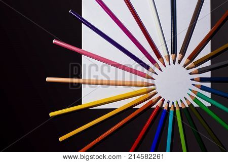 Multicolour pencils and sheet of paper on black background. Art and creativity concept. Copy space