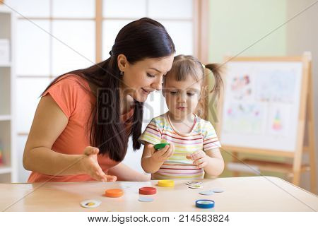 Woman teacher play with preschooler child in day care center