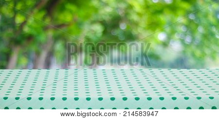 Empty table cover with green polka dot tablecloth over blur green nature park background banner table top counter design for food and product display montage