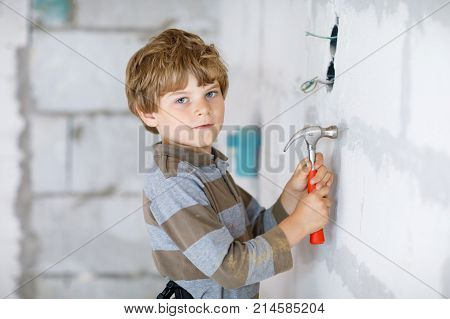 Little kid boy helping with toy tools on construction site. Funny child of 6 years having fun on building new family home. Kid with nails and hammer helping father to renovate old house