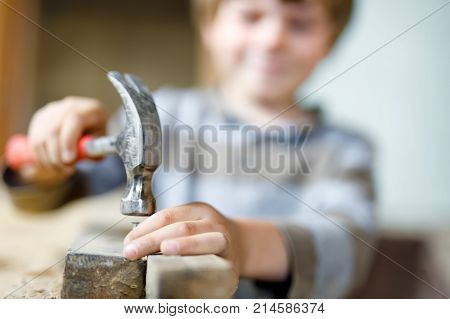 happy little kid boy helping with toy tools on construction site. Funny child of 7 years having fun on building new family home. Kid with nails and hammer. Selective focus on hands and tools