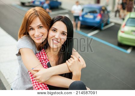 Two atractive young girlfriends hugging, laughting and sitting near road in the street. one girl in red plaid shirt, another redhead girl in gray shirt and blue skirt. concept of sincere friendship