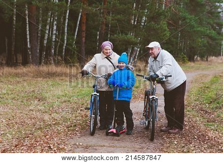 grandparents on bikes with grandson on schooter ride in nature, grandparenting