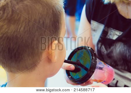 Young Boy Drinks Sweet Shaved Ice At Ice Cream Parlor
