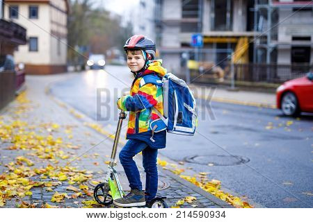 cute little school kid boy riding on scooter on way to elementary school. Child with safety helmet, school bag on rainy autumn day. Traffic in the city and schoolchildren