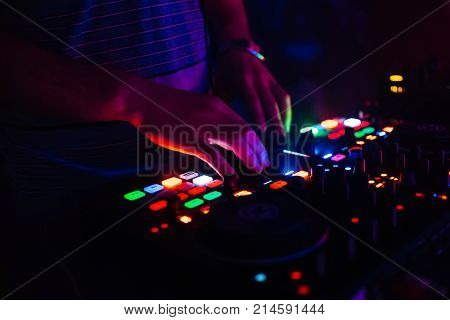 hands of modern DJ professional mixer and music Board of the controlling buttons and levels club music