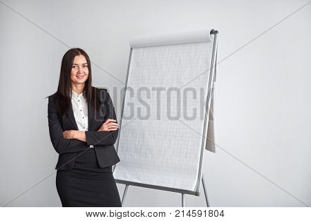 Portrait of young smiling businesswoman standing by flipchart in office.