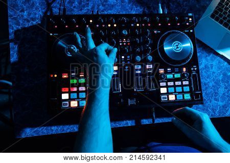 hands of DJ and professional music equipment, mixer buttons and controlling the levels of music and blue lighting