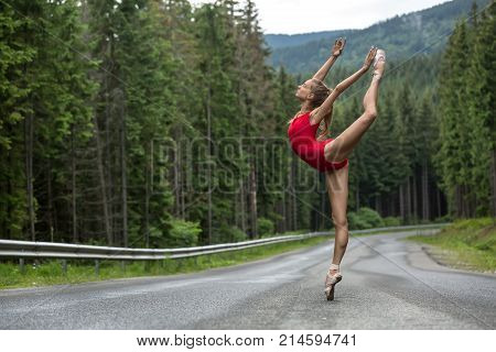 Beautiful ballerina stands on the right toe on the roadway on the coniferous forest background. Her arms and the left leg outstretched upwards. She wears a red leotard and light pointes. Horizontal.