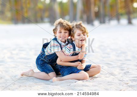 Two lovely little brothers sitting on sand on tropical beach, happy best friends, kids boys playing, friendship concept. Siblings brothers, twins in family look with palms. Family vacations