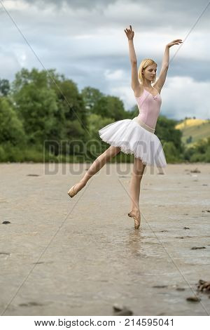 Beautiful ballerina posing on the left toe in the shallow river on the background of green shore and cloudy sky. She wears a white tutu, pink leotard and beige pointes. Her arms outstretched upward.