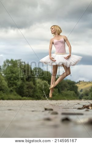 Gorgeous ballerina jumping in the shallow river on the background of green shore and cloudy sky. She wears white tutu, pink leotard and beige pointes. Water splashes spreading around her legs.
