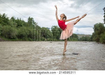 Stylish ballerina stands on the right toe with outstretched arms in the shallow river on the background of green shore and cloudy sky. She wears a peach tutu, red leotard and beige ballet shoes.