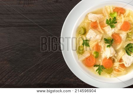 An overhead closeup photo of a plate of chicken, vegetables, and noodles soup, shot from above on a dark rustic texture with a place for text