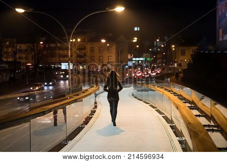 Back view of young brunette woman, going late night on the pedestrian mirror bridge in city Rzeszow in city centre, country Poland, soft focus.