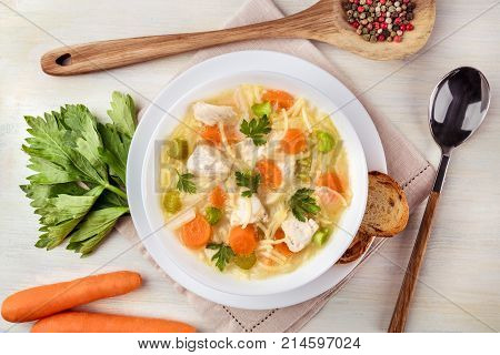A closeup photo of a plate of chicken and noodles soup, shot from above on a light texture with a spoon, a wooden ladle with peppercorns, slices of bread, a celery branch, and carrots