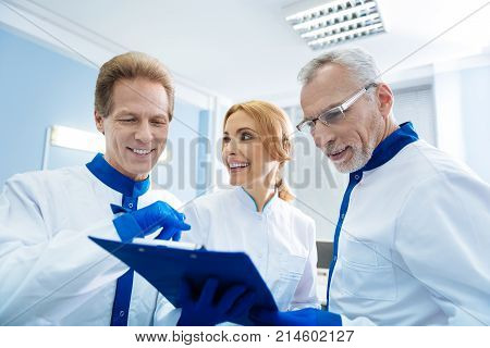 Breakthrough. Happy professional experienced biologists smiling and discussing gene analysis results while being in the lab
