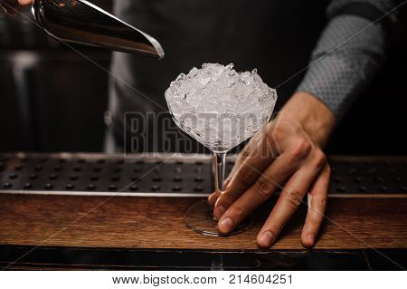 Barmans hand holding a cocktail glass filled with ice cubes on the wooden bar counter