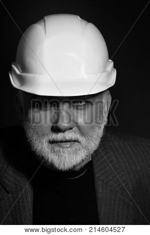 Handsome bearded old man with blue eyes and silver moustache on serious face in white hard hat on black background