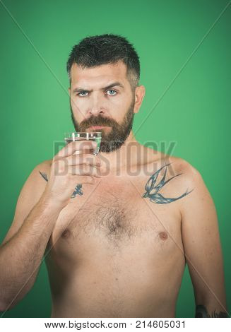 Health and dieting. Man with long beard hold water glass on green background. Hangover and thirst. Hipster drink clean healthy water refreshing. Life source and healthcare. poster