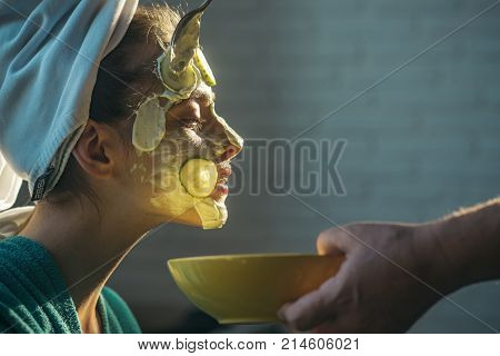 Skin care spa wellness. Beauty salon concept. Cosmetician hands with spoon and bowl. Rejuvenation health youth. Girl or woman get cucumber mask on face.