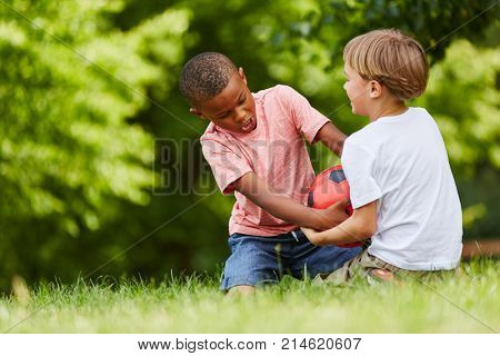 Two boys scuffle for soccer ball in match in the park