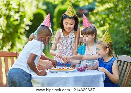 Many children together celebrating wtih birthday cake at kids party