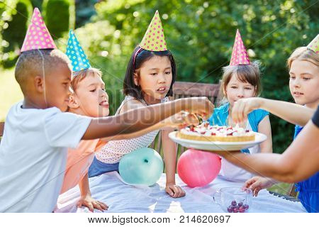Many interracial kids eating cherry pie at birthday party in summer