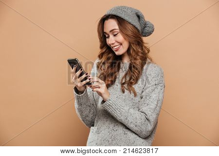 Close-up of gorgeous young woman in winter clothes chatting on mobile phone, isolated on beige background