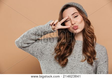 Picture of smiling young lady on winter warm hat isolated and looking camera make peace gesture.
