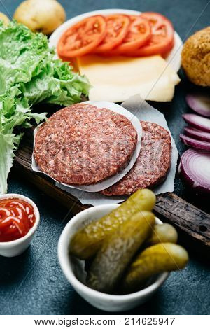 Preparation beef burger with lettuce and ripe tomatoes, cheese and red onion. Ingredients for delicious fresh homemade burger