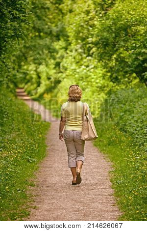 A woman walking down a footpath on a bright sunny day