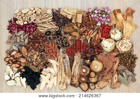 Traditional chinese herbs used in alternative herbal medicine on bamboo background. Top view.