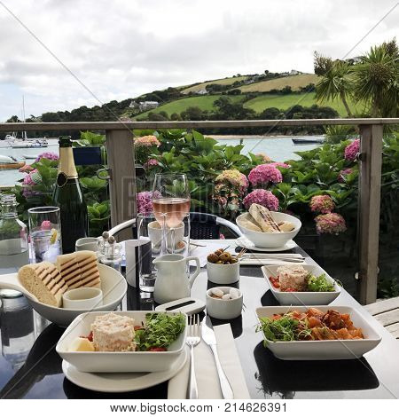 Spanish tapas gourmet al fresco lunch selection with wine on a restaurant table overlooking countryside and a river.