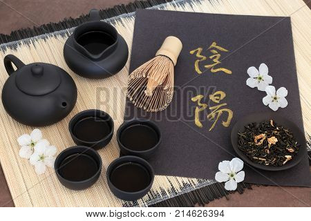 Chinese jasmine tea with yin and yang chinese calligraphy script, cherry blossom, teapot, cups, jug, whisk and dried leaves on bamboo mat. Translation reads as yin yang.