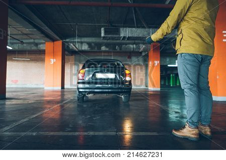 unconfident young woman parking car on empty spot in underground parking with man help