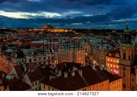 Rooftop evening view of typical buildings of Old Town and Prague Castle on background.