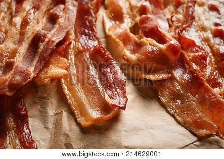 Cooked bacon rashers on parchment, closeup