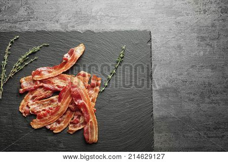 Slate plate with cooked bacon rashers on table