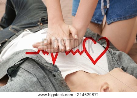 Woman giving first aid to man with heart attack outdoors