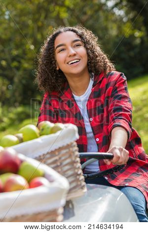 Beautiful happy girl teenager female young woman smiling with perfect teeth in an orchard driving a tractor with baskets of organic apples she has been picking